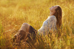 woman sitting in the warm sunshine in field